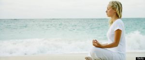 Woman meditating on tropical beach