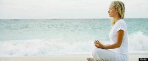Woman meditating on tropical beach